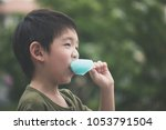 cute asian child eating blue... | Shutterstock . vector #1053791504