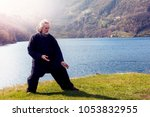 mature man practicing tai chi... | Shutterstock . vector #1053832955