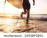 man surfer run in ocean with... | Shutterstock . vector #1053892841