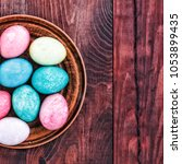 easter eggs in a clay plate on... | Shutterstock . vector #1053899435