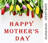 """Small photo of Floral background, greeting card, harvesting, mocap for greetings for mother's day, international women's day: multi-colored tulips on a light background, copyspace inscription: """"Happy mothers day"""""""