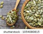 pumpkin seeds in a wooden plate ... | Shutterstock . vector #1054080815