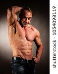 bodybuilder pose in studio over ...   Shutterstock . vector #1054098119