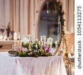 Small photo of A table for two. Romantic atmosphere in subdued light, lighted candles and rustic decoration (forest moss, flowers, glasses and vases)