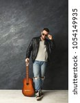 Small photo of Stylish rocker with guitar at gray background. Handsome man in brutal lather jacket and sunglasses having fun at studio. Fashion, hobby and musician concept, copy space