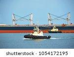 tugboat assisting bulk cargo... | Shutterstock . vector #1054172195
