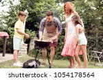 family having a barbecue party... | Shutterstock . vector #1054178564