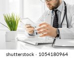 doctor writes out the pills to... | Shutterstock . vector #1054180964