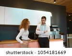 candid shot of two coworkers... | Shutterstock . vector #1054181669