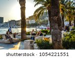 Small photo of Split, Croatia - September 29 2017: Late afternoon at the Riva Promenade at the harbor of Split Croatia as tourists enjoy watching boats at sea and relax under the palm trees on the Adriatic Coast