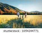 family walk on the field near... | Shutterstock . vector #1054244771
