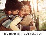 parents hugging their little... | Shutterstock . vector #1054363709