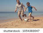 father and son playing football ... | Shutterstock . vector #1054383047