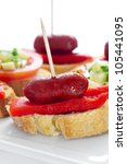 closeup of a plate with spanish pinchos made with chorizos an red pepper - stock photo