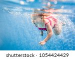 Small photo of Little baby, girl swimming under water in paddling pool. Diving baby. Learning infant child to swim. Enjoy of swimming and bubbles.