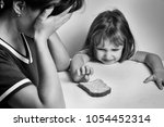 Small photo of A depressed mother and a hungry daughter pulling her hand to a piece of bread. families with low incomes. crisis