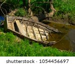 old boat lying on the bank of... | Shutterstock . vector #1054456697