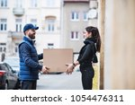 woman receiving parcel from... | Shutterstock . vector #1054476311