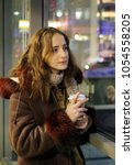 Small photo of A young girl in a warm jacket with a hood warms her hands with a paper glass with hot coffee. City life. Fuzzy urban background.