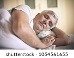 senor man sleeping on bed at... | Shutterstock . vector #1054561655