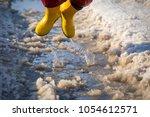 kid in yellow rainboots jumping ... | Shutterstock . vector #1054612571