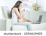 young mother holding a year old ... | Shutterstock . vector #1054619405