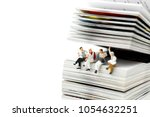 Small photo of Miniature people: Businessman reading newspaper and sitting on book using as education or relax business concept.