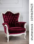 Small photo of Red velour wood armchair in white room