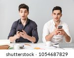 two shocked young men using... | Shutterstock . vector #1054687829