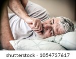 senior man lying in bed and... | Shutterstock . vector #1054737617