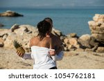 couple stand at rocky sea beach ... | Shutterstock . vector #1054762181