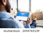 a man holding a tablet with... | Shutterstock . vector #1054765139