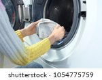 young woman doing laundry in... | Shutterstock . vector #1054775759