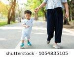 asian mother walks with her... | Shutterstock . vector #1054835105