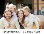 happy parents piggybacking son... | Shutterstock . vector #1054877105