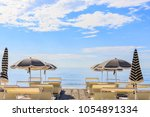 beach umbrellas and couches on... | Shutterstock . vector #1054891334