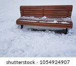 park bench in winter snow | Shutterstock . vector #1054924907