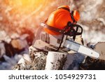 chainsaw and protective helmet... | Shutterstock . vector #1054929731