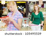 women choosing food produces in shopping mall with supermarket trolley - stock photo