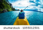 woman paddles kayak in the lake ... | Shutterstock . vector #1055012501