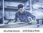 carpenter is painting a wood... | Shutterstock . vector #1055061944