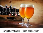 two glasses of fresh pale beer... | Shutterstock . vector #1055083934