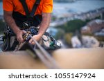 Close up pic of male rope access job industrial worker, using a working safety device descender on static twin ropes abseiling, repairing windows at rise building in  Sydney city CBD, Australia  - stock photo