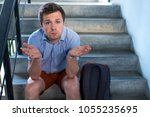 a young man is sitting on the... | Shutterstock . vector #1055235695