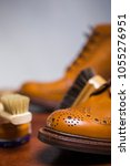 Small photo of Footwear Concepts and Ideas.Extreme Closeup of Tips of Premium Male Brogue Tanned Boots with Lots of Cleaning Accessories on Foreground.Vertical Image