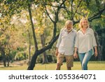 senior couple smiling and... | Shutterstock . vector #1055364071