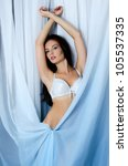 Beautiful girl in underwear a background of blue fabric - stock photo
