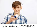 Small photo of Happy young man in a blue checkered shirt with a fashionable haircuttalking on cell phone isolated on white background. mobile phone on which is attached modern holder for phone pop socket