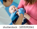 baby on mothers hand at... | Shutterstock . vector #1055392061