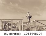 Rear view roofer builder on wooden roof trusses construction. Worker with carpenter tool belt working balancing on roofing. New home site house foundation framing in Irving, Texas, USA. Vintage - stock photo